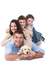 Happy family lying on top of each other with dog