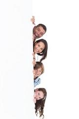 Happy family hiding behind billboard
