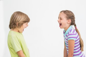 Siblings laughing on white background