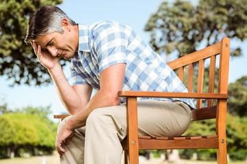 Upset man sitting on park bench