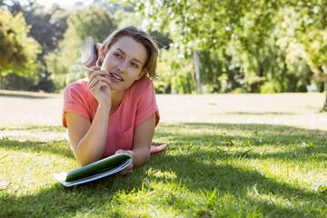Pretty woman reading book in park