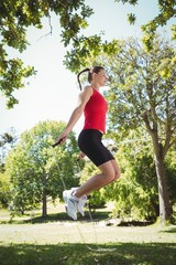 Fit woman skipping in the park