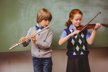 Students playing flute and violin in classroom