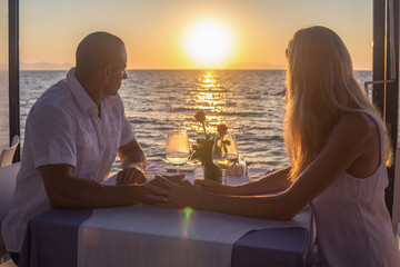 Couple viewing sunset in sea restaurant