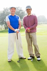 Golfing friends smiling at camera holding clubs