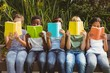 Children reading books at park - 79075887