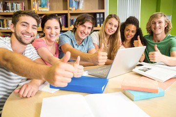 College students gesturing thumbs up in library