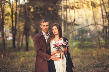 Young couple on autumn background. Future family
