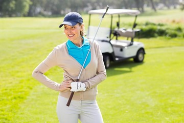 Female golfer smiling with hands on hip