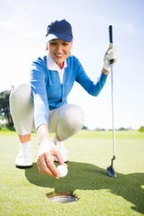 Smiling lady golfer kneeling on the putting green