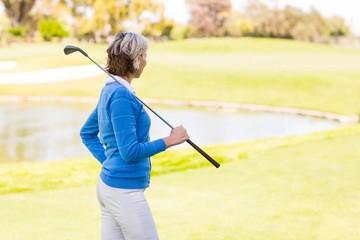Female golfer standing holding her club