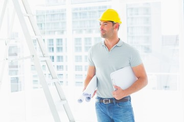 Handyman with blueprints and clipboard in office