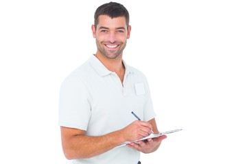 Smiling male handyman writing on clipboard