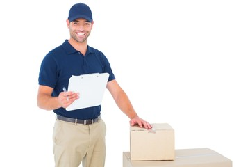 Happy delivery man with cardboard boxes and clipboard