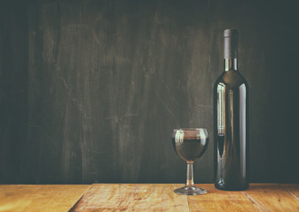 bottle of red wine and wine glass over wooden table. image is fi