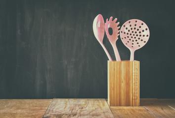 kitchen utensils over wooden textured background