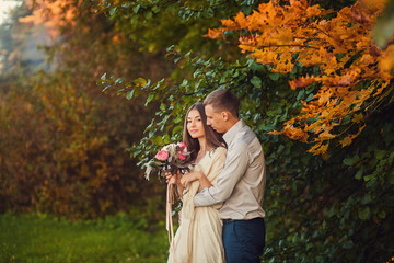 sweet couple in autumn park on a background of bright leaves