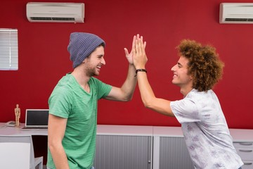 Casual young businessmen high fiving in office