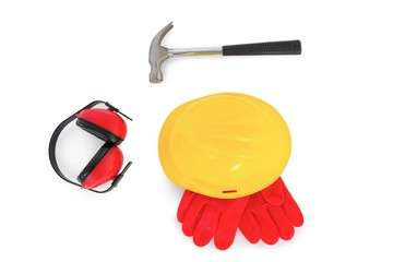 Hardhat with gloves, earmuffs and hammer on white