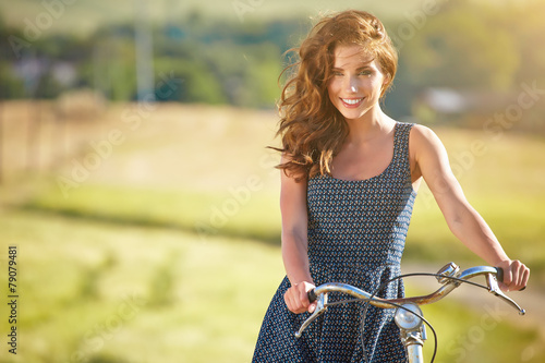 Sexy woman with vintage bike in a country road. - 79079481
