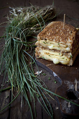 double sandwich with omelette and chives on rustic table