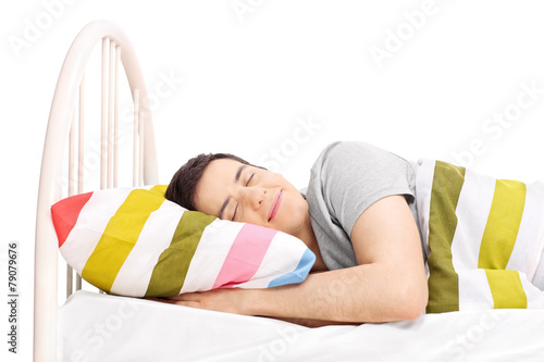 Studio shot of a carefree man sleeping in bed - 79079676