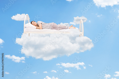 Man sleeping on a bed in the clouds - 79079692