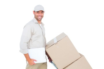 Delivery man pushing trolley of boxes on white background