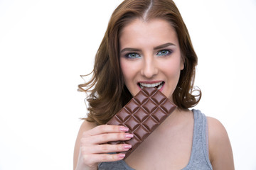 Happy woman biting in a chocolate tablet over white background
