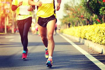 marathon runner legs running on street