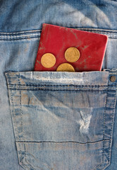 Old jeans with coins and passport in pocket