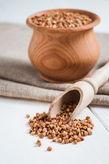 buckwheat in a wooden bowl on white background