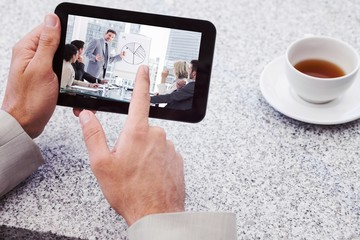 Composite image of businessman using small tablet at table
