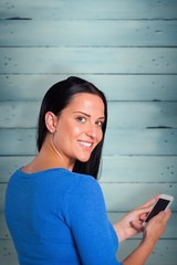 Composite image of young brunette sending a text