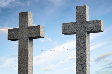 Two concrete crosses against sky and trees