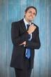 Composite image of thinking businessman holding pen