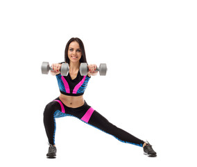 Pretty girl doing fitness exercise with dumbbells