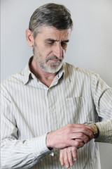 Portrait of a man looking at the time on his wrist watch