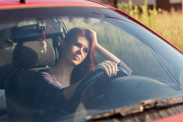 Dissatisfied, tired woman driving a car holding his head