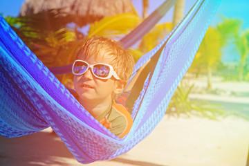 happy little boy relaxed in hammock on the beach