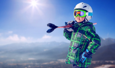 Boy in full ski equipment on the mountain view