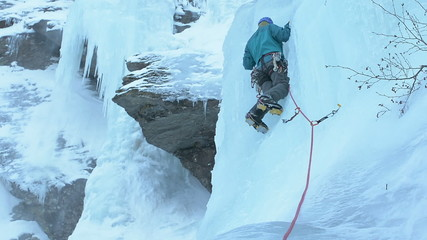 Ice climber placing ice screw high up