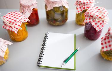Notepad among jars of pickled vegetables