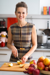 Portrait of happy young housewife cutting apple in kitchen