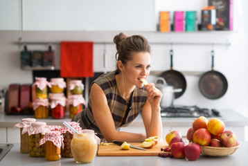 Young housewife standing near jars with fruits jam