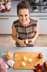 Portrait of happy young housewife cutting apple for jam