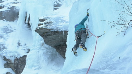 Ice climber on steep waterfall winter