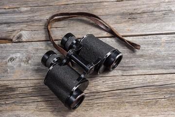 vintage binoculars on wooden background