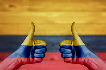 Colombia flag painted on female hands thumbs up