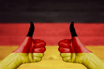 Germany flag painted on female hands thumbs up
